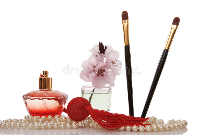 Pearls beads, perfume, two cosmetics brush royalty free stock photography