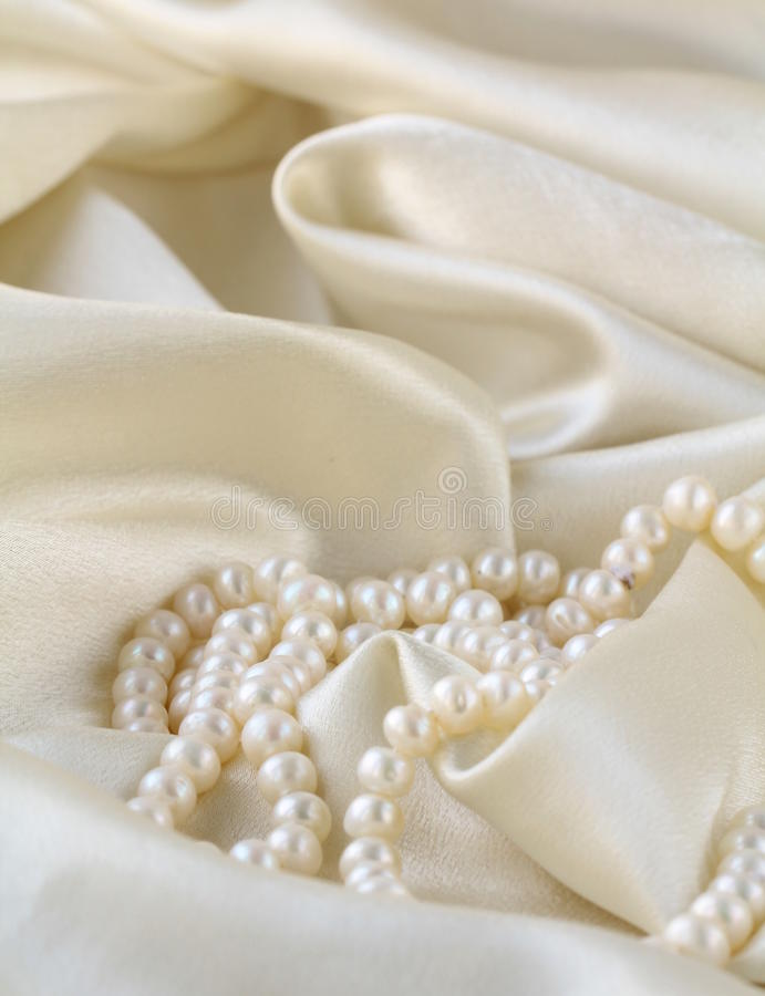 Pearls a necklace on a silk. Fabric stock photography