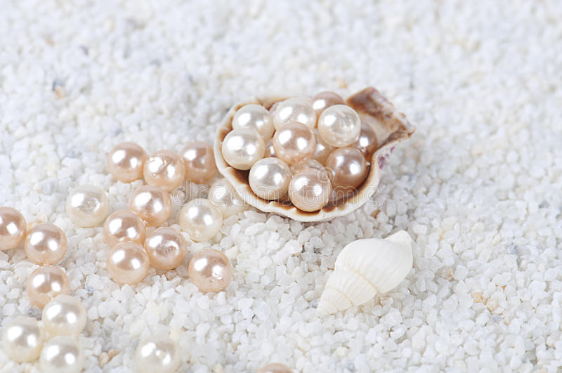 Pearls in the sea shell on the sand royalty free stock photo