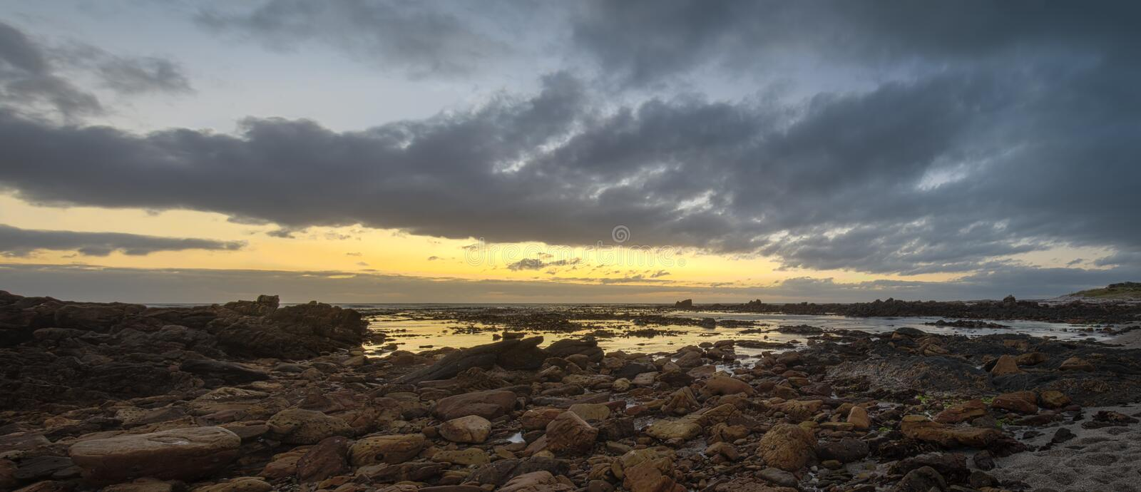Pearly Beach Panorama. The photo is taken during sunrise on the east coast of South Africa, with overcast skies. It is a lateral Panorama of a bay at low tide royalty free stock photo