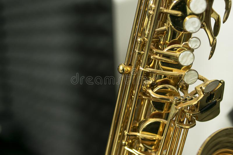 Pearly keys of a golden and shiny tenor saxophone. Close-up of the keys of a golden and shiny tenor sax where you can see the constructive details of the musical stock image
