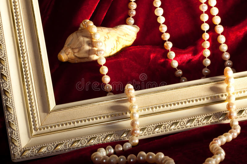 Pearly necklace. A pearly necklace is running out of the mussel over the frame on a satin red cloth royalty free stock photos