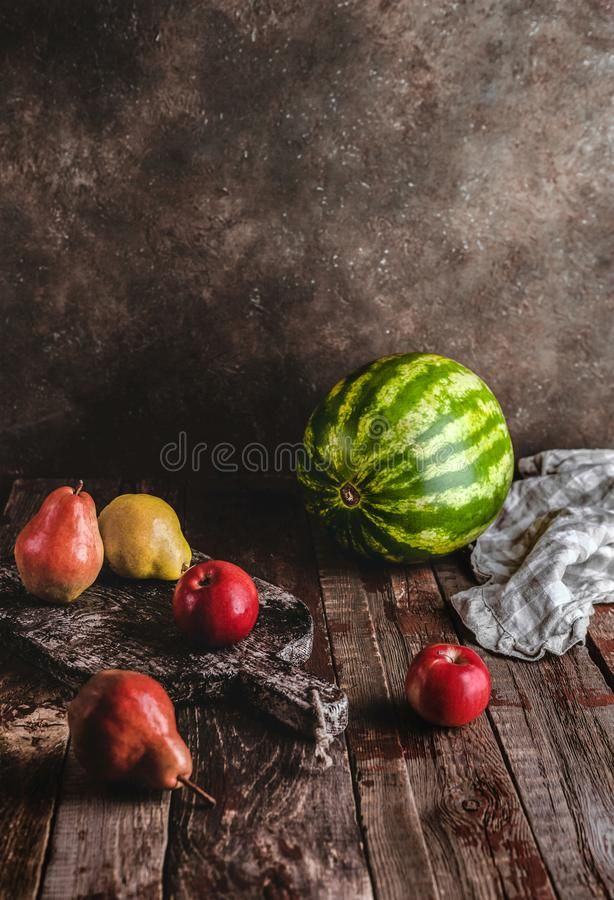 pears, apples, watermelon, kitchen towel and cutting board stock photo