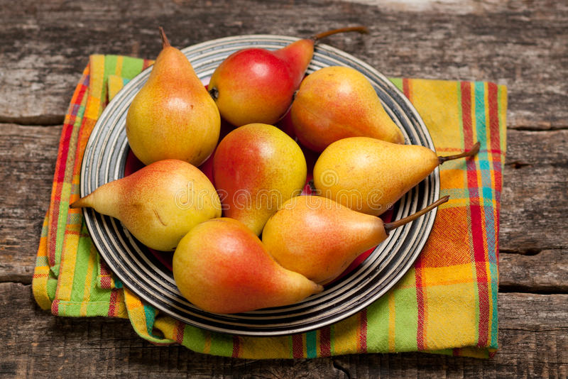 Pears on the dish and cloth on the old wood backing royalty free stock photography