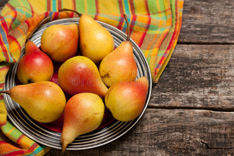 Pears on the dish and cloth on the old wood backing royalty free stock photos