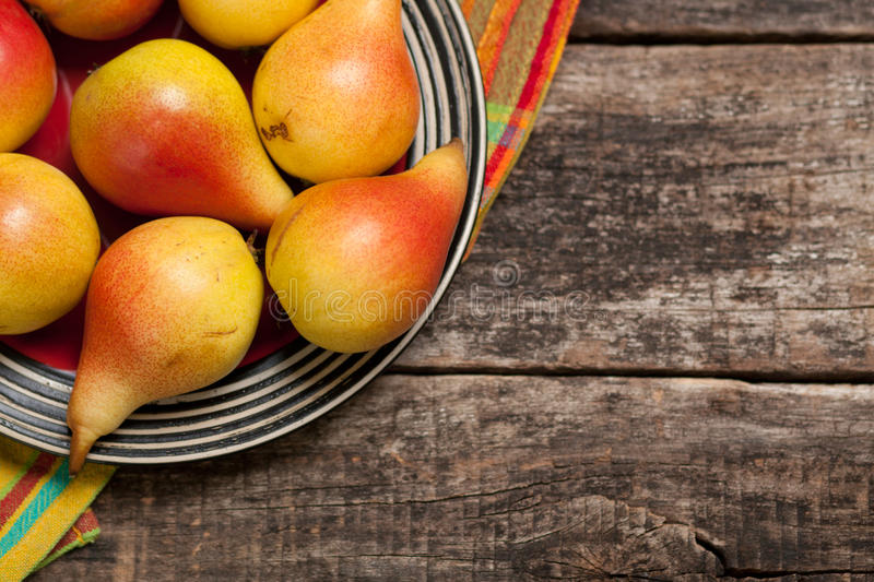 Pears on the dish and cloth on the old wood backing royalty free stock images