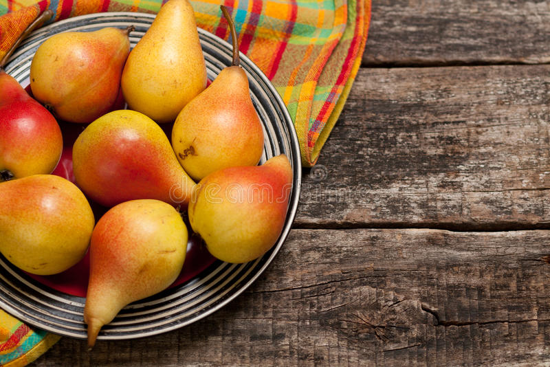 Pears on the dish and cloth on the old wood backing stock photo
