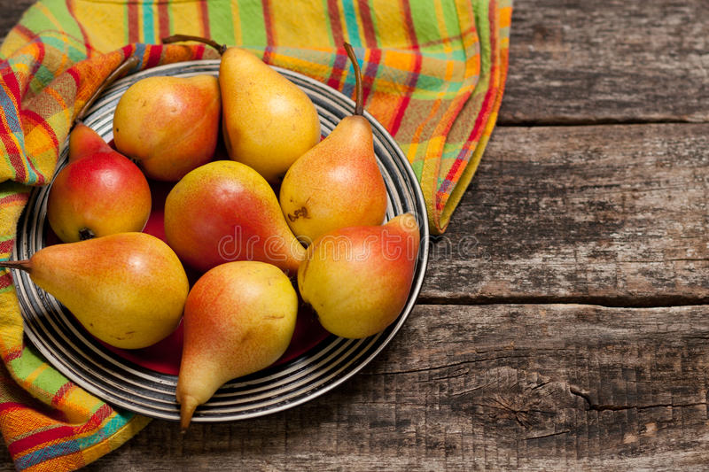 Pears on the dish and cloth on the old wood backing royalty free stock image