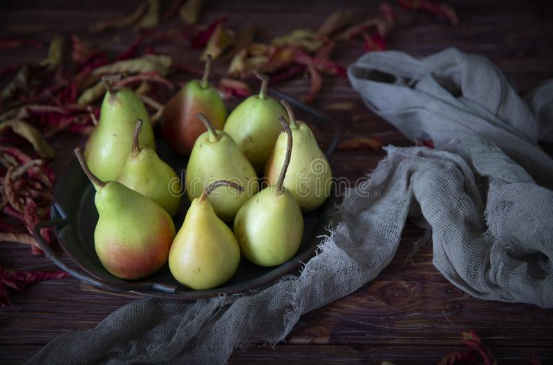 Pears on a tray and autumn dried leaves. stock images