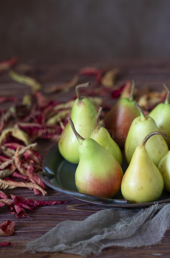 Pears on a tray and colorful dried leaves. royalty free stock photography