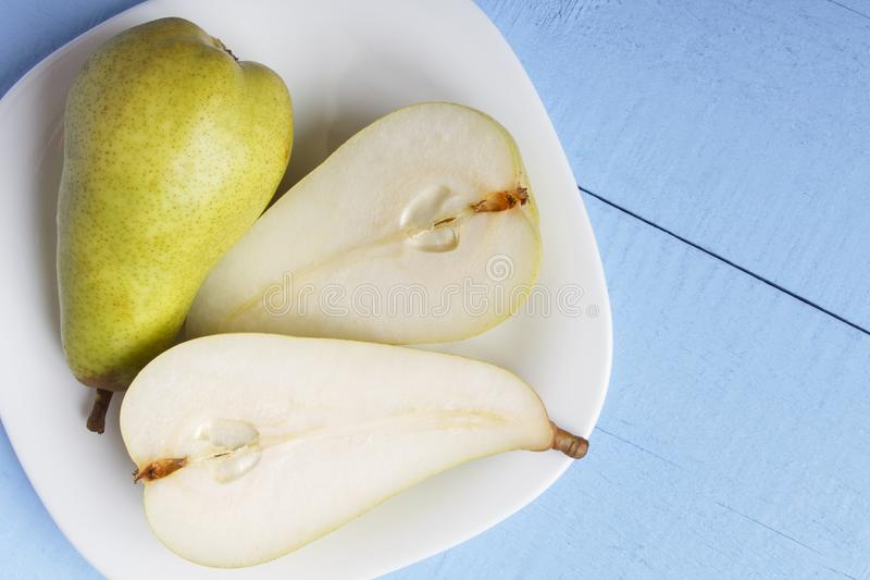 Pears on white plate in closeup. View from above on wooden table. Copy space. Healthy vegetarian food concept stock photos