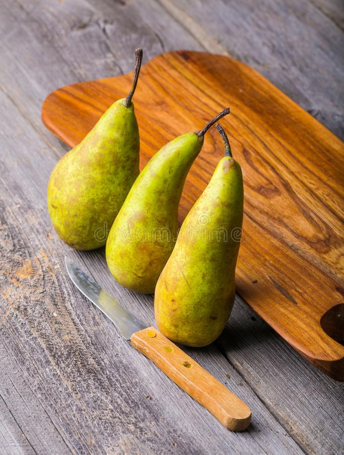 Pears on wooden cutting board. And ancient wooden table. Studio shot royalty free stock photography
