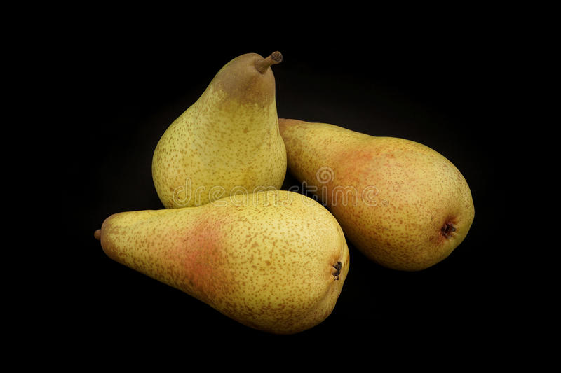 Pears of yellow color on a black background closeup stock image