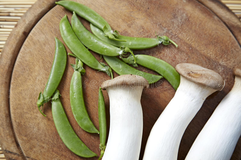 Peas with mushrooms. Wooden chopping board royalty free stock photography
