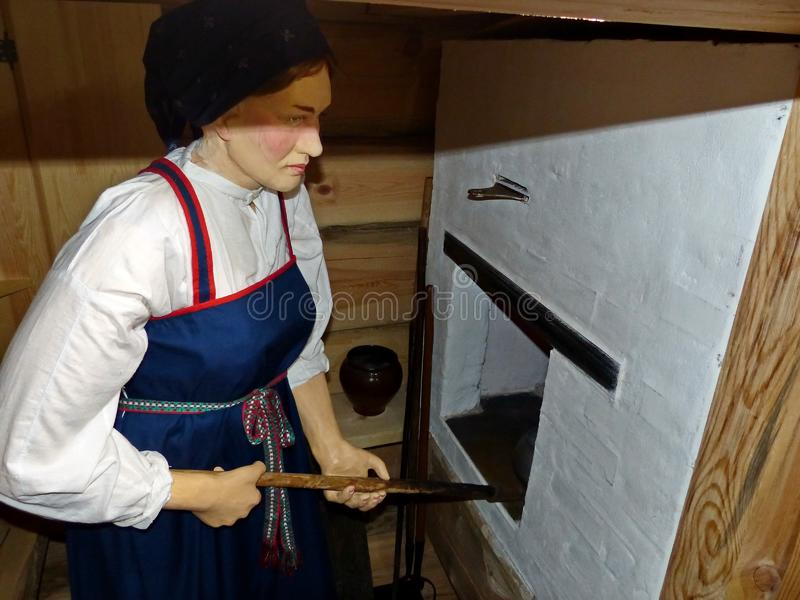 In the peasant hut. Mistress near the Russian stove. royalty free stock photography
