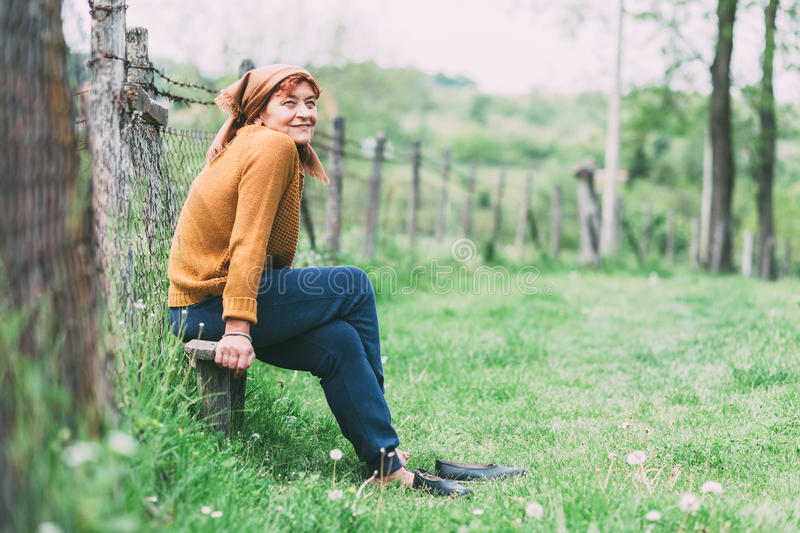 Peasant mature woman sitting on the bench stock photos