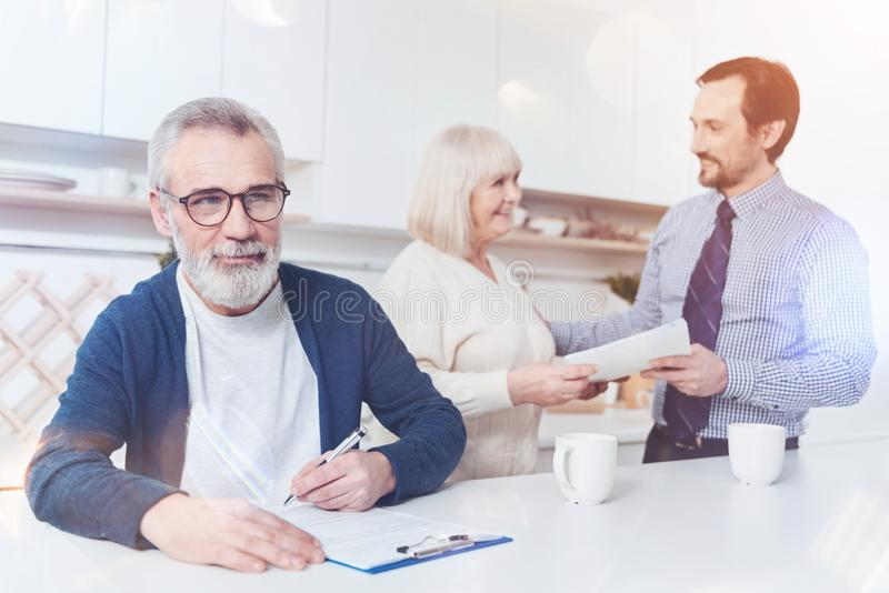 Peasant thoughtful man signing papers. Put it here, Pleasant thoughtful aged men sitting in the kitchen and signing papers while his wife talking with real royalty free stock photos