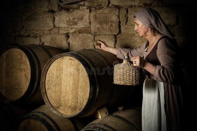 Peasant woman in medieval wine cellar royalty free stock photo
