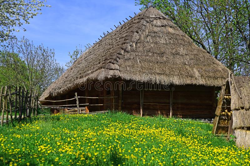 Peasants hut. Country house on spring landscape. Old village cottage. Building made of wood with thatched roof stock photos