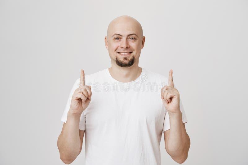 Peased knap Kaukasisch gebaard mannetje die ruim terwijl het wijzen omhoog op met beide wijsvingers glimlachen, die bevinden zich royalty-vrije stock foto's