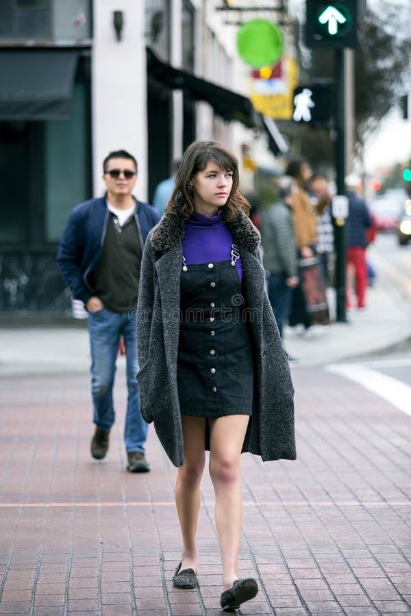 Peatón femenino que camina en un paseo cruzado en una ciudad foto de archivo libre de regalías