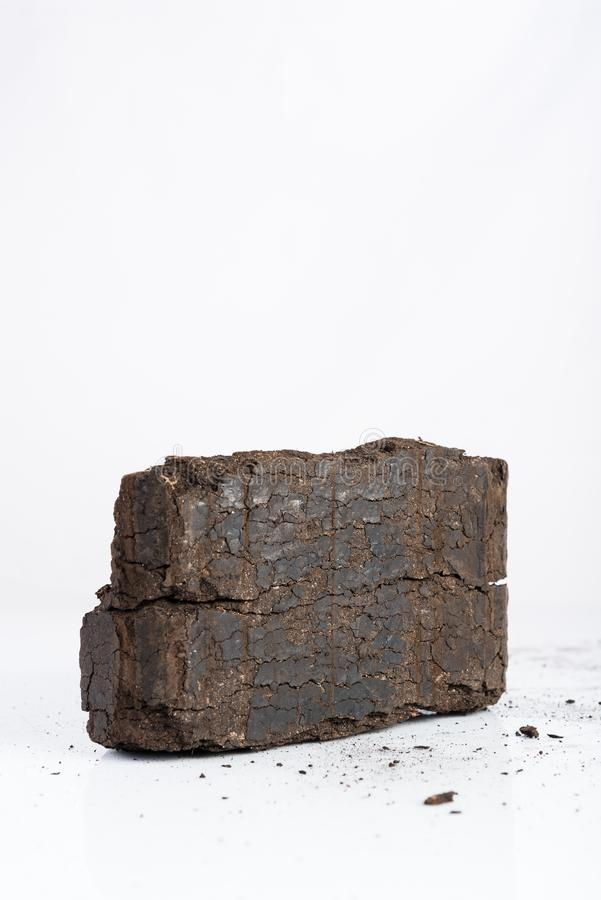 Peat briquette on white background, alternative fuels, place for text. Peat briquette on white background, alternative fuels, raw material, place for text royalty free stock images