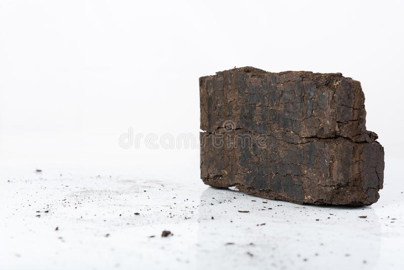 Peat briquette on white background, alternative fuels, place for text. Peat briquette on white background, alternative fuels, raw material, place for text royalty free stock photography