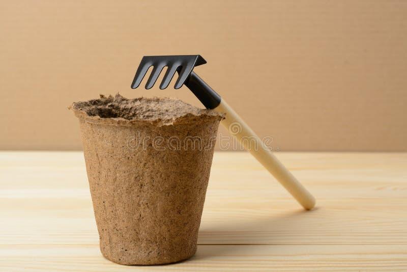 Peat pot and rake. Peat pot for seedlings and small rake royalty free stock image
