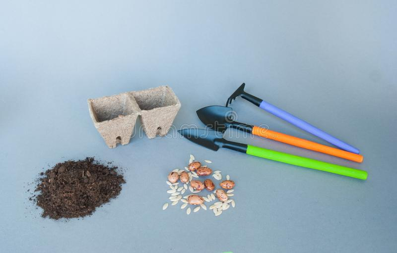 Peat pots with garden tools and soil stock image
