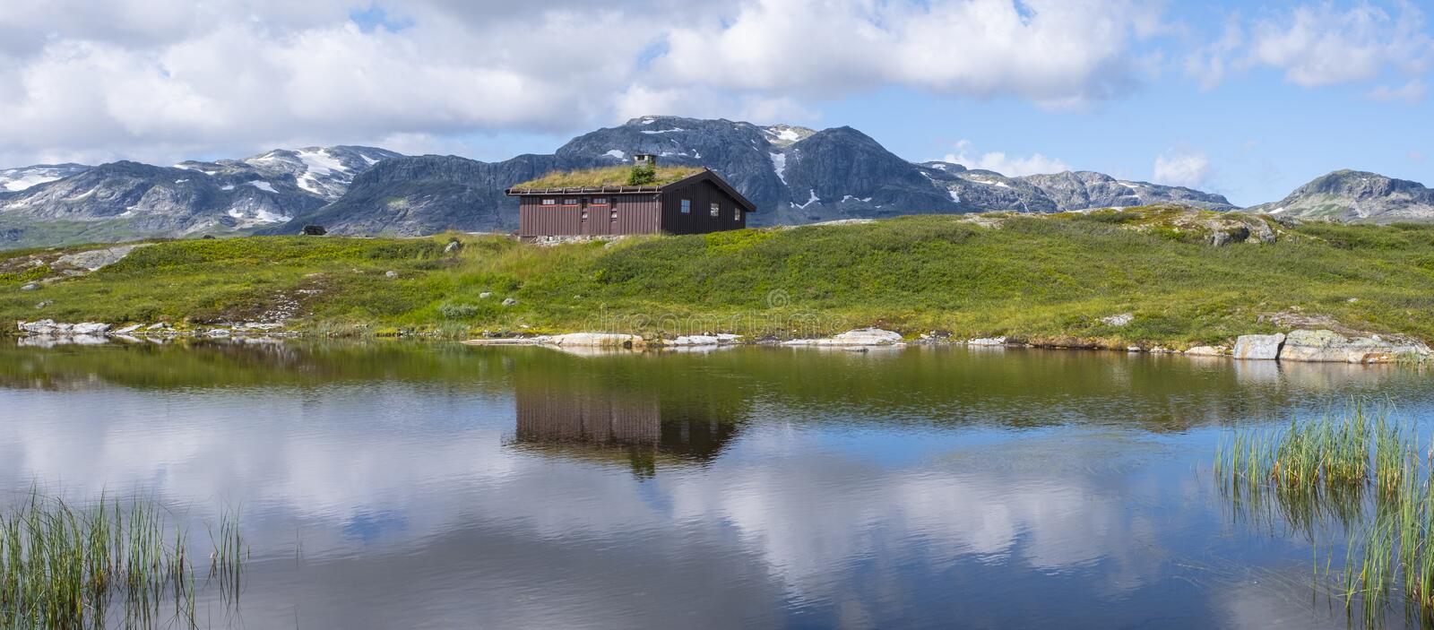 Peat roofed hut on Lake Stavatn with mountains reflected in it royalty free stock images