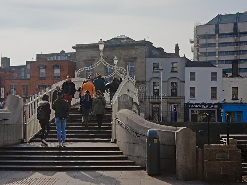 Peatones en el puente famoso del medio penique en Dubl?n fotos de archivo