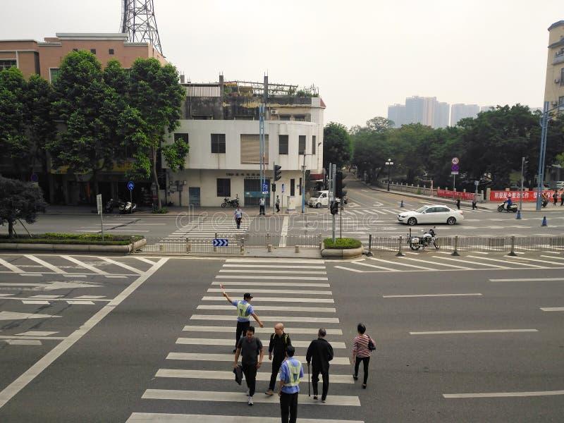 Peatones principales de la policía auxiliar que caminan a través del camino imagen de archivo