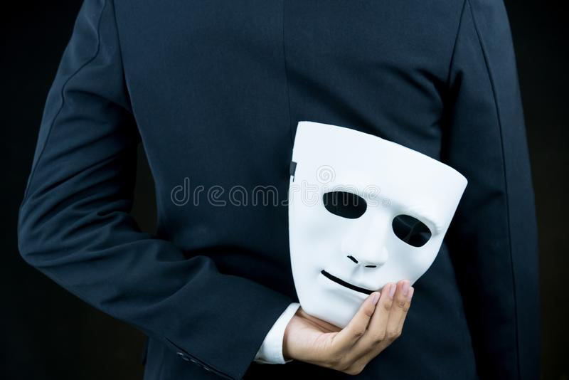 Peau d'homme d'affaires le masque blanc dans la main derrière son dos sur b photo libre de droits
