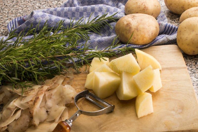 Peau et pomme de terre organique crue de coupe avec le romarin photographie stock