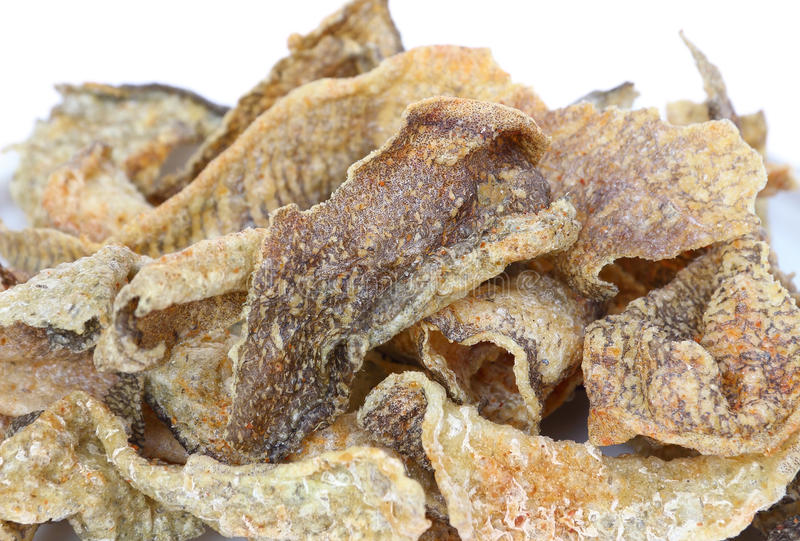 Peau frite croustillante de poissons avec des épices sur le fond blanc photographie stock
