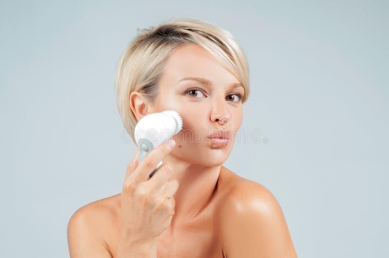 Peau heureuse de visage de nettoyage de femme avec la brosse Beauté et station thermale image stock