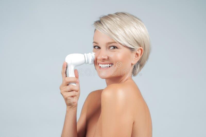 Peau heureuse de visage de nettoyage de femme avec la brosse et la mousse Beauté et station thermale photographie stock libre de droits