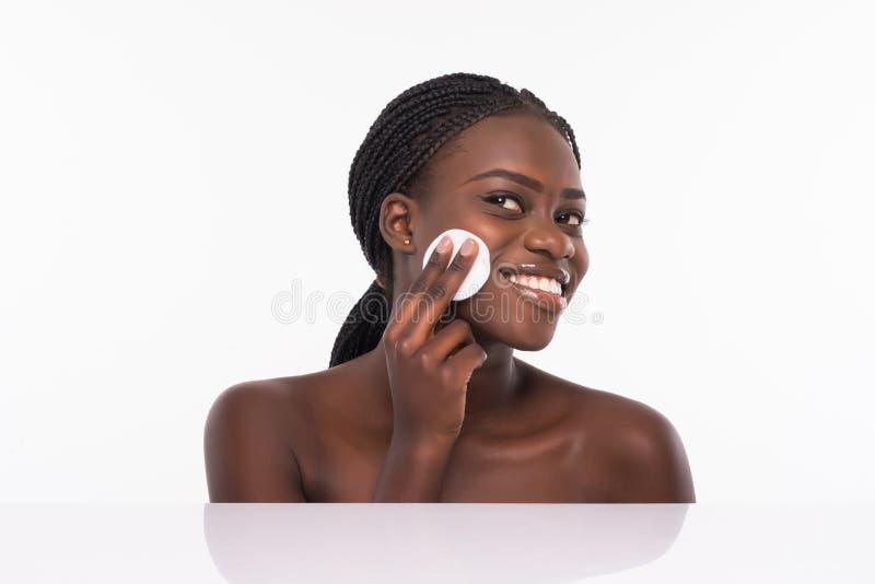 Peau propre de belle jeune femme africaine avec l'éponge de beauté Maquillage nu naturel d'isolement sur le fond blanc Massage fa photo libre de droits