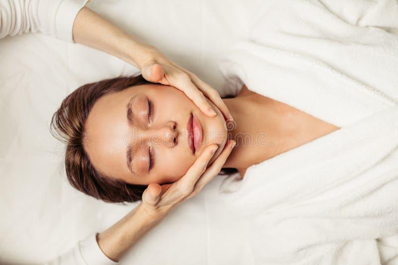 Peau saine de visage jeune belle fille recevant un massage pour le visage photographie stock