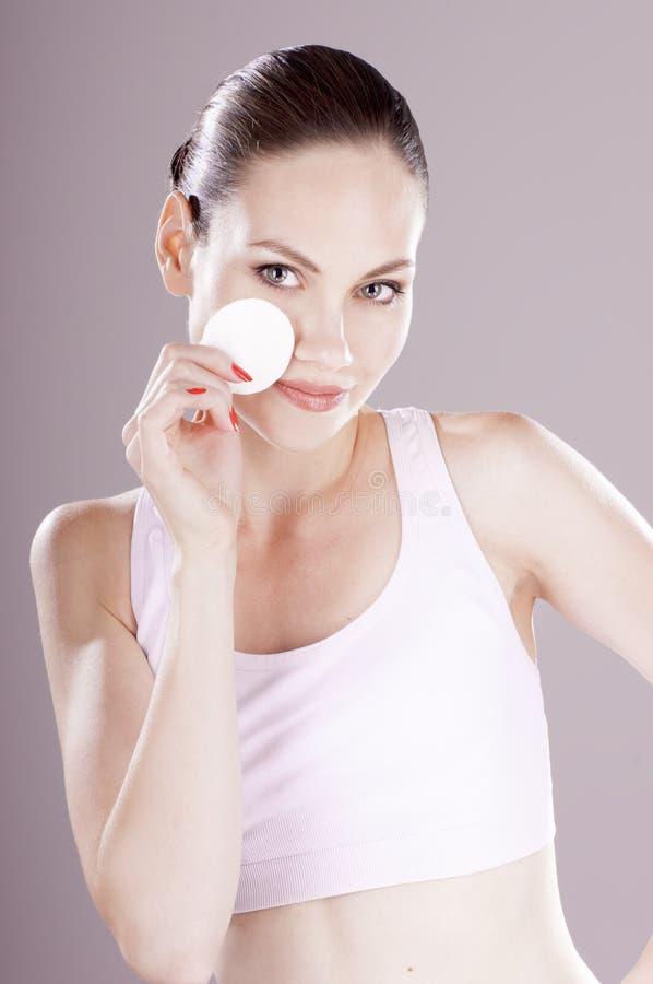Peau sensuelle de nettoyage de jeune femme avec le tampon de coton photographie stock libre de droits