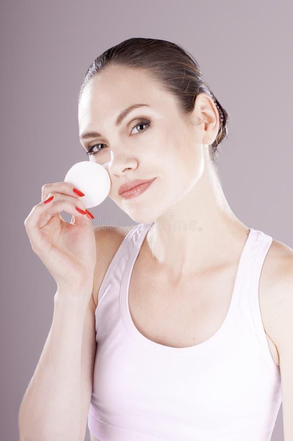 Peau sensuelle de nettoyage de jeune femme avec le tampon de coton photo stock