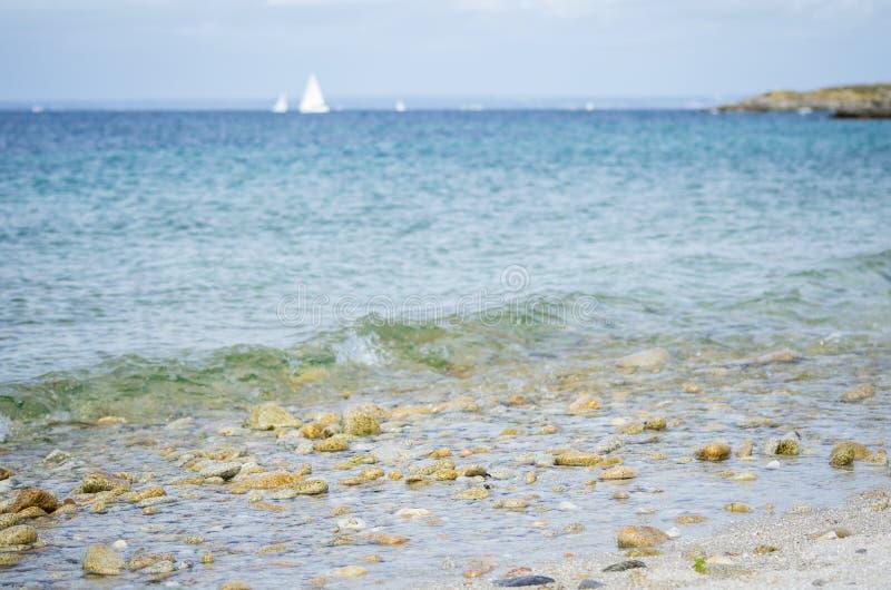 Pebble海滩,有蓝色海和白色小船的在背景中 免版税图库摄影