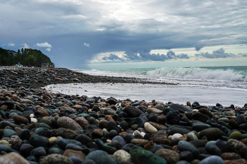 Pebble beach on the black sea. Beautiful clouds over the sea before the rain. Surf wave. Abkhazia. Georgia stock image