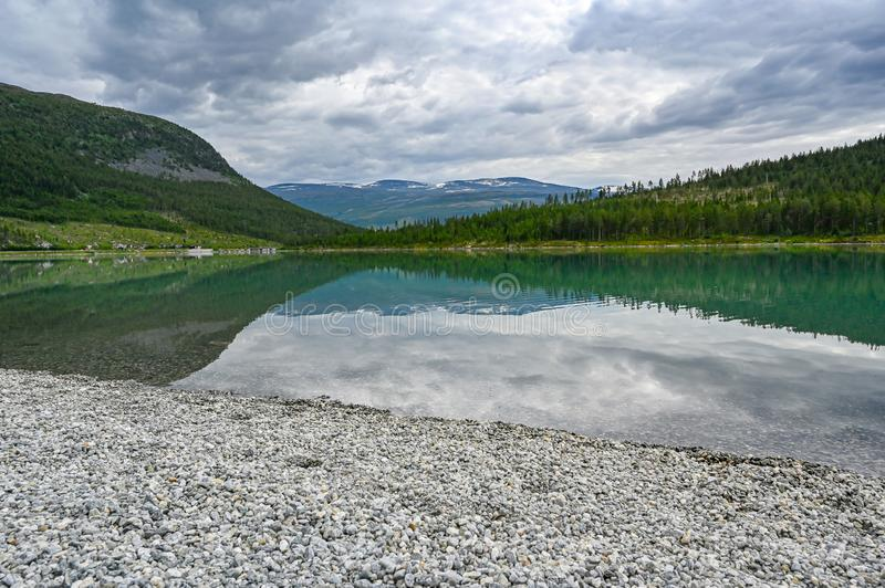 Pebble beach and calm lake in Norwegian mountains. July 2019 stock image