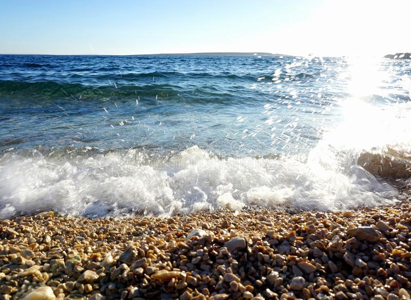 Pebble beach with sun reflection in the wavy sea water and white foam royalty free stock photography