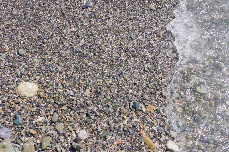 Pebble coastline. Seashore with transparent water and small stones.  royalty free stock images