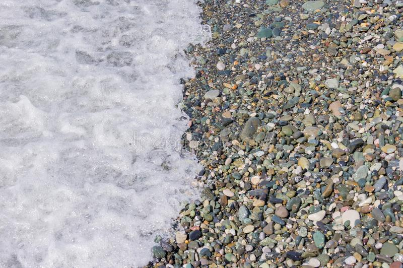 Pebble coastline. Seashore with transparent water and small stones.  royalty free stock photos