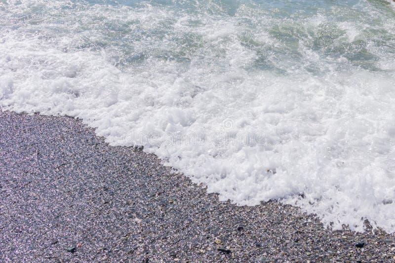 Pebble coastline. Seashore with transparent water and small stones.  stock photo