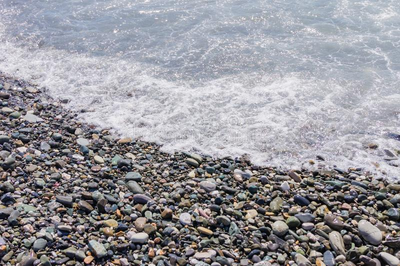 Pebble coastline. Seashore with transparent water and small stones.  stock photography