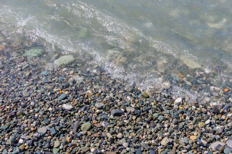 Pebble coastline. Seashore with transparent water and small stones.  stock image